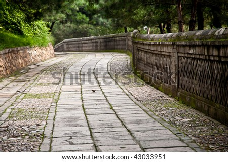 An old stone path in the woods - stock photo
