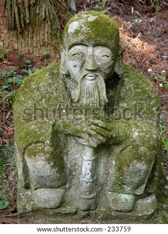 an old stone statue covered by moss