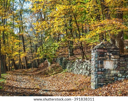 An old stone wall in this Bucks County Pennsylvania woodlands. - stock photo