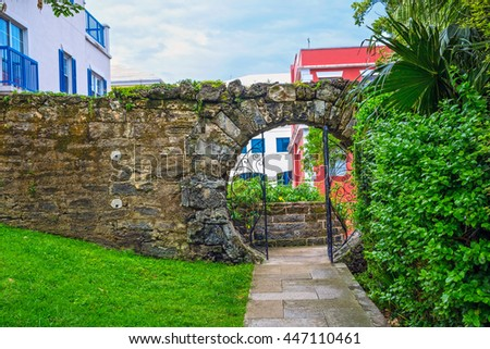 An old stone wall with a moon gate in Queens Park, Hamilton Bermuda. - stock photo