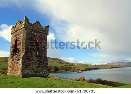 An old stone  Watch tower over looking Dingle Bay Co. Kerry Ireland as a fishing boat heads out to sea. - stock photo