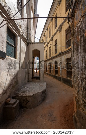 an old stonetown zanzibar street scene showing a back alleyway through rustic worn down building exteriors. - stock photo