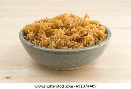 An old stoneware bowl filled with fusilli whole wheat organic pasta on a wood table top. - stock photo