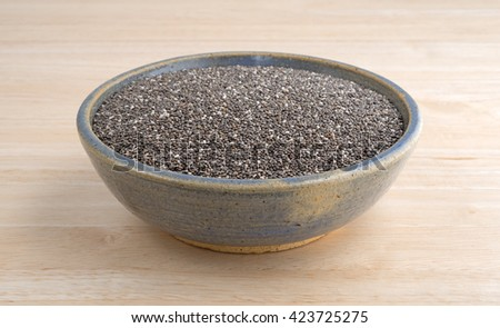An old stoneware bowl filled with organic chia seeds on a wood table top. - stock photo