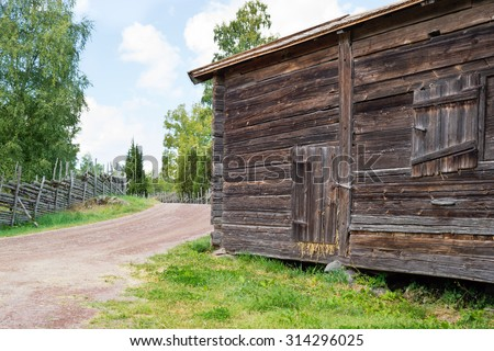 An old storage building by the roadside. Building is storing hay. Hay is sticking out from the door and very little from the closed window. Country road passes by on the left. Old fences at roadside. - stock photo