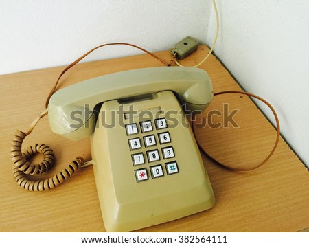 An old style digital telephone on wooden table in the corner of room. - stock photo