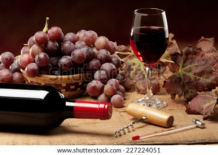 An old table with a bottle of wine, vine leaves, and red grapes - stock photo