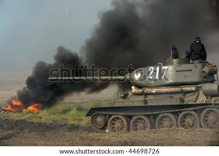 An old tank in action, some grey smoke and soldier sitting on the top of tank. - stock photo
