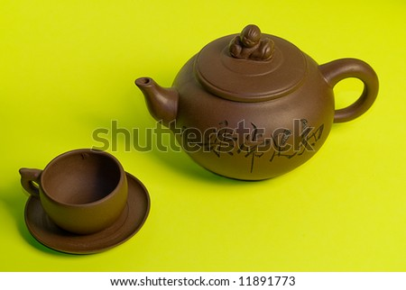 An old teapot sitting beside a cup and saucer