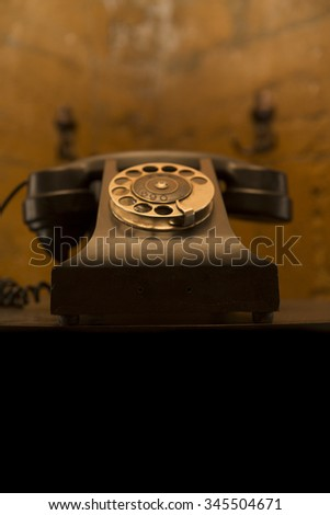 an old telephon with rotary dial. Old-fashioned phone on vintage background. Retro black old phone on the table. antique   - stock photo