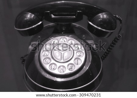 An old telephone with a rotary dial mechanism  - stock photo