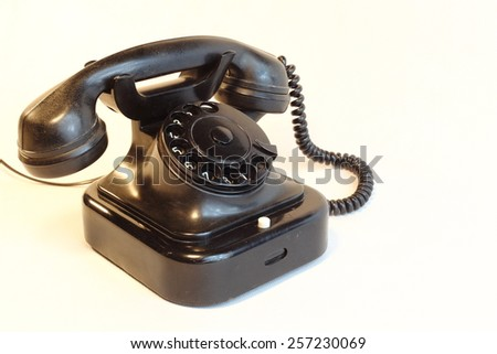 an old telephone with rotary dial / Old rotary phone on white background