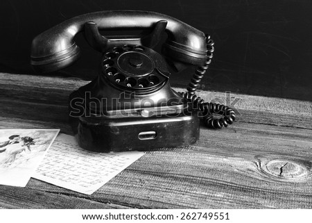 an old telephone with rotary dial/ old telephone on wood / vintage style - stock photo