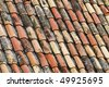 An old tile roof with moss growing, typical design and construction of the late 19th century. - stock photo
