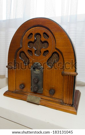 An old time classic radio on wooden shelf.