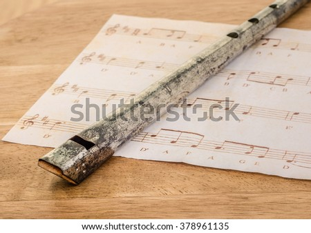 An old Tin Whistle and sheet music on an oak desk. - stock photo