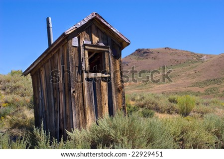An old toilet or 'outhouse' sitting in the middle of nowhere, evoking memories of the past
