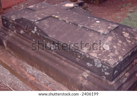 An old tomb with a cross top, and iron fittings. Very vampiric. - stock photo