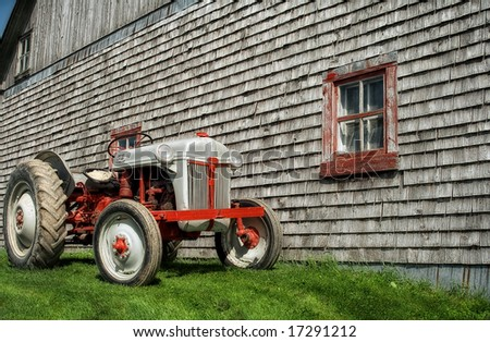 An old tractor in front of a barn - stock photo