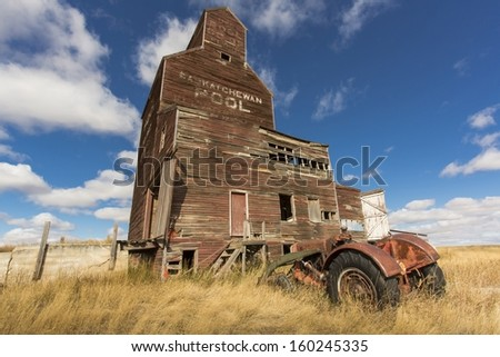 An old tractor rusts away near a grain elevator in the ghost town of Bents, Saskatchewan - stock photo