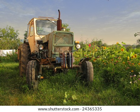 An old tractor standing on the field - stock photo