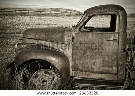 An old truck rusting in the field - stock photo