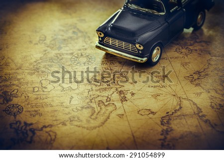 An old truck toy on a Treasure map background - stock photo
