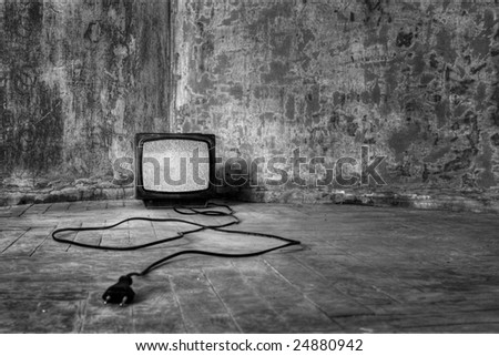An old TV with the noise on its display standing on the dirty floor - stock photo
