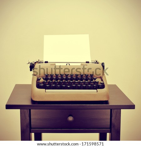 an old typewriter with a blank page on a desk, with a retro effect - stock photo