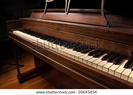 An old unused piano in a darkened hall. - stock photo