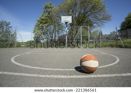 An old used basketball at the top of the key on an outdoor basketball court on a sunny day - stock photo