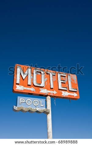 An old vintage, neon sign points to a motel that was never built.  Lots of copy space. - stock photo