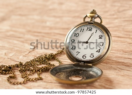 an old vintage pocket watch on grungy paper - stock photo