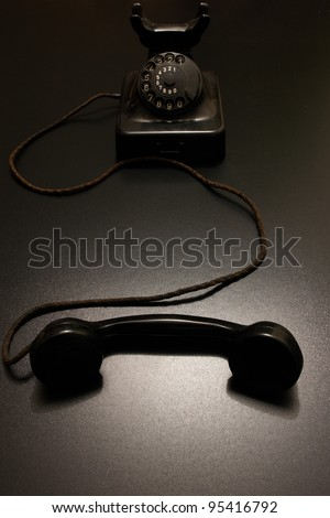 an old vintage telephone in dramatic lighting. - stock photo
