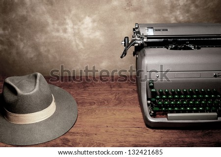 An old vintage typewriter with a reporter's fedora hat on a wooden table with room for copy. - stock photo