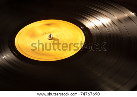 An old vinyl LP playing on a turntable. Good background for music designs. - stock photo