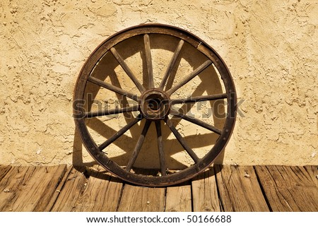 An old wagon wheel sits on a wooden sidewalk and leans against a stucco wall, in a scene from the American West.  The wheel casts interesting shadows against the wall. - stock photo