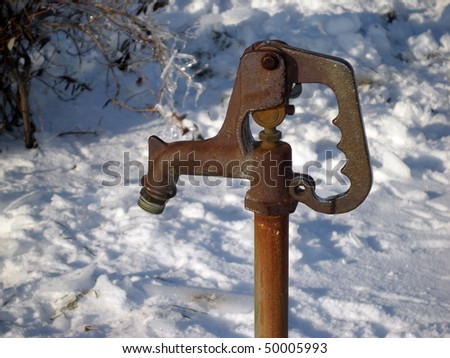 An old water pump in a snowy scene. - stock photo