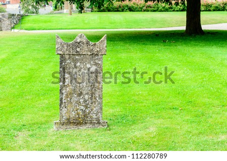 An old, weathered and lonely tomb stone on a green well cut lawn.
