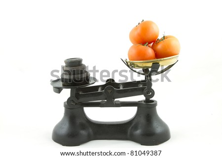 An old weighing scales painted black with a brass bowl containing tomatoes all isolated on white.