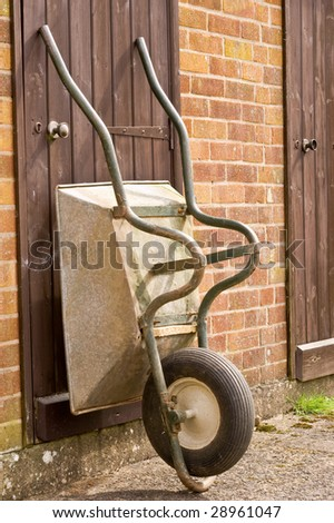 an old well used and worn wheel barrow propped against a wooden shed door. - stock photo