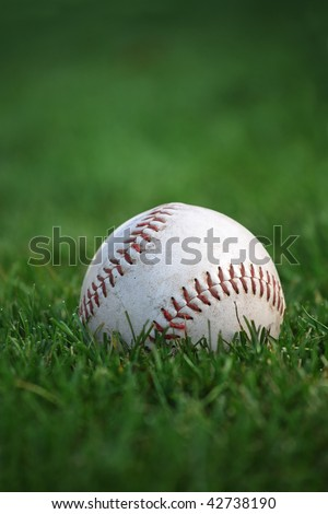 An old well-used baseball sitting in the grass of the outfield. Plenty of space for text. Selective focus on red stitches. - stock photo