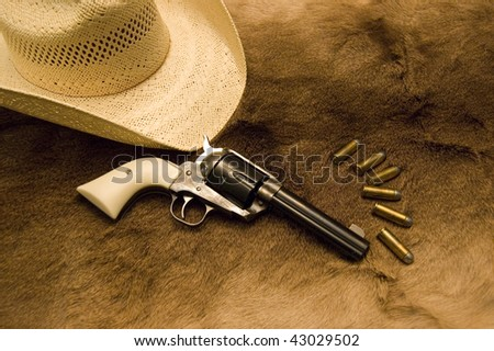 An old western revolver with ammo and a hat on top of an old deer skin
