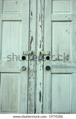 An old white door with padlocks