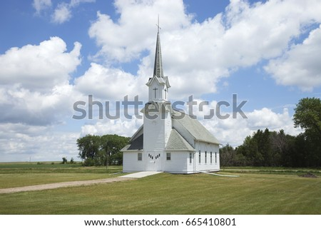 An old white wooden church with steeple on the prairie