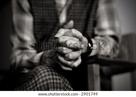 An old widow is praying while mourning her late husband - stock photo