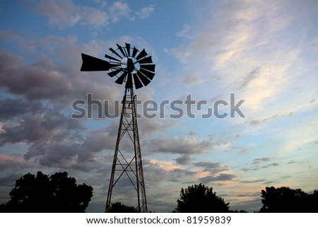 An old windmill in silhouette set against the setting sun.