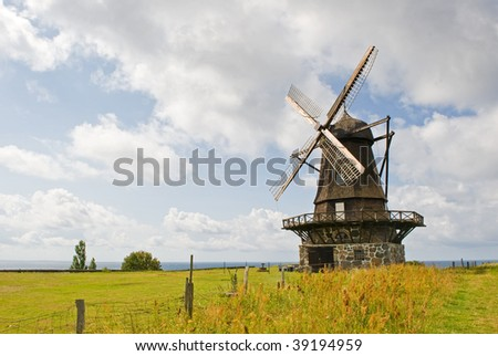 An old windmill is shown in a rural area. There are no people viewable. Horizontally framed shot. - stock photo
