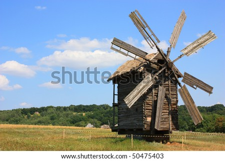 An old windmill standing in a field, summer