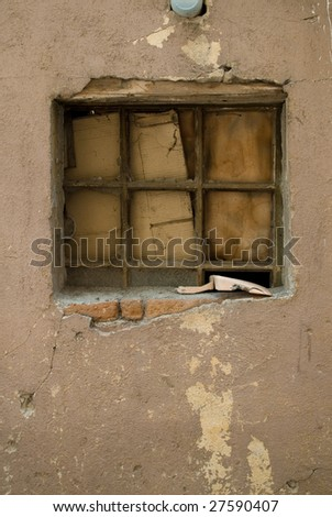 An old window covered with cardboard and a scoop on the window pane. - stock photo
